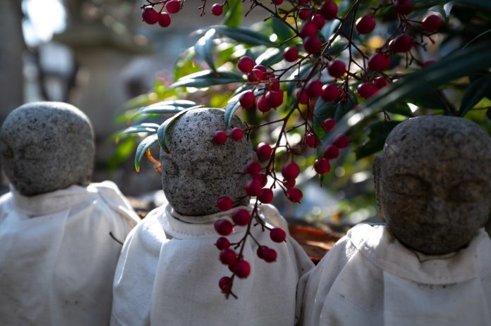 statue of 3 monks with a flowering plant hanging near by