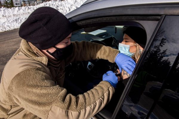 A soldier vaccinates a woman in her car at a vaccination center in Londonderry, New Hampshire on February 4, 2021. Concerning data of COVID-19 vaccine miscarriages and stillbirths are present in the CDC's Vaccine Adverse Event Reporting System (VAERS)