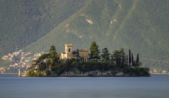 Little island Isola di Loreto on Iseo Lake at sunrise, Italy.