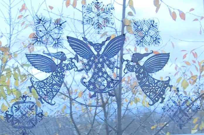 A papercutting of angels and snowflakes hanging in a window.