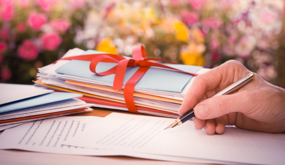 A person holding a fountain pen over a sheet of paper with a stack of evelopes tied with a red ribbon beside them on a desk with pink, yellow, and white flowers in the background.
