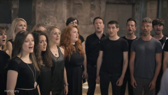 London Contemporary Voices: group of young people mainly wearing black in warehouse space with light browns on the wall singing together.
