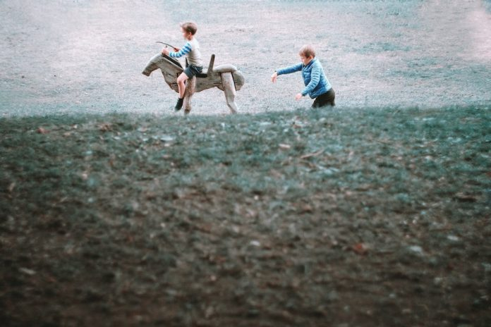 boy chasing another boy who rides a wooden horse in a field