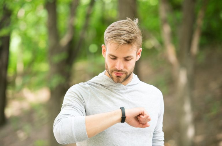 A young man in the woods checking his fitness tracker.