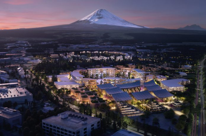 An artist's rendering of Toyota's new smart city, aerial view, at night, with Mount Fuji in the background.
