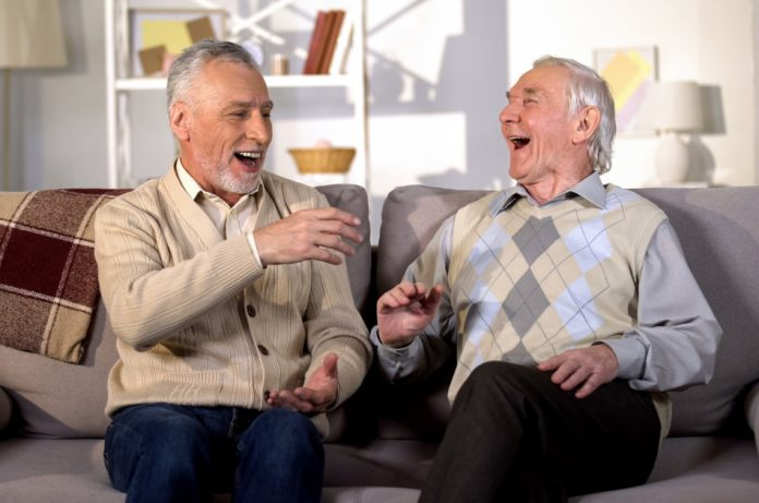 Aged brothers laughing while sitting on a sofa together.