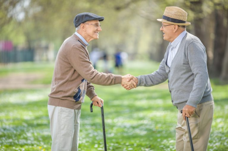 Two elderly men wearing cardigans and hats and holding canes shake hands.