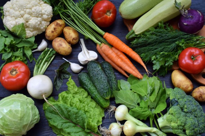 Fresh organic green leafy vegetables, carrots, zucchini, potatoes, onions, garlic, cauliflower, tomatoes, potatoes, turnips, and herbs seen against a dark blue surface.