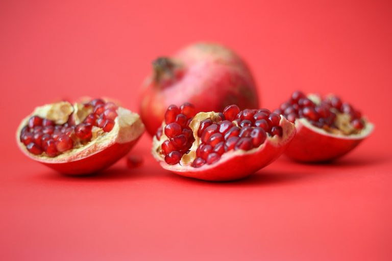 open pomegranate on pink background