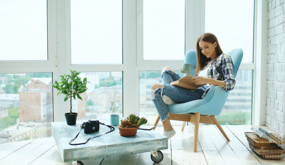 Young woman reads a book sitting on the balcony in a modern loft apartment.