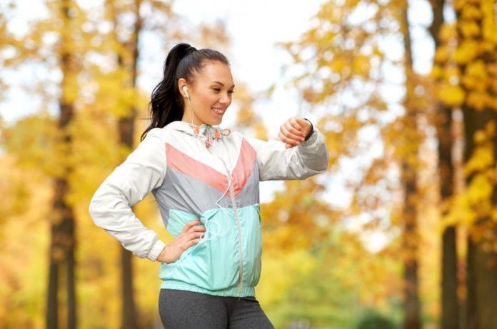 A woman looking at her fitness tracker while running in the park in Autumn.