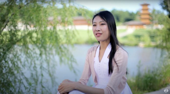 Chinese dancer from Shen Yun sits with lake and traditional building behind her she wears white and pale pink and has long black hair