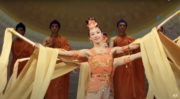shen yun dancer in orange and yellow costume with long yellow sleeves and headpiece and male dancers dressed in orange robes with blue hair in the background.