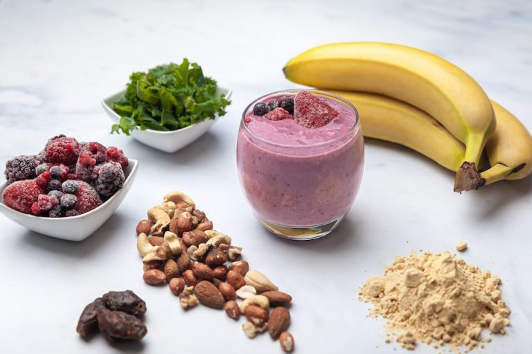 pink fruit smoothie in glass surrounded by healthy ingredients bananas, protein powder, frozen berries, nuts, bowl of greens, dates