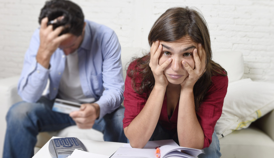 Young couple sitting on a couch going over finances with worried and stressed looks on their faces.