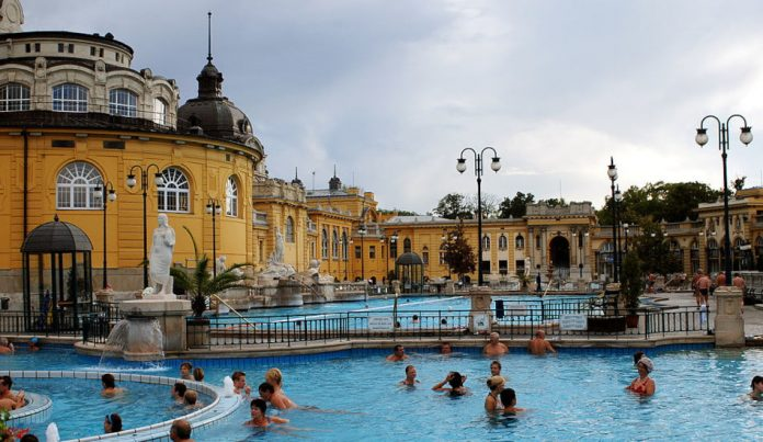 People in the water outside at the Budapest thermal spa Széchenyi Gyógyfürdő.