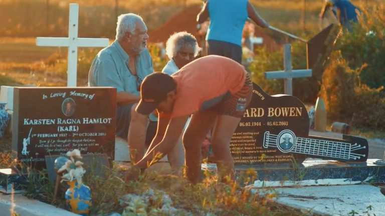 young boy weeding weeds from grave and older couple sitting in chair behind him