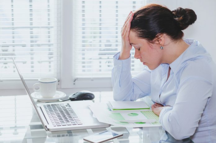 Tired woman with laptop at her desk, appearing stressed by problems.