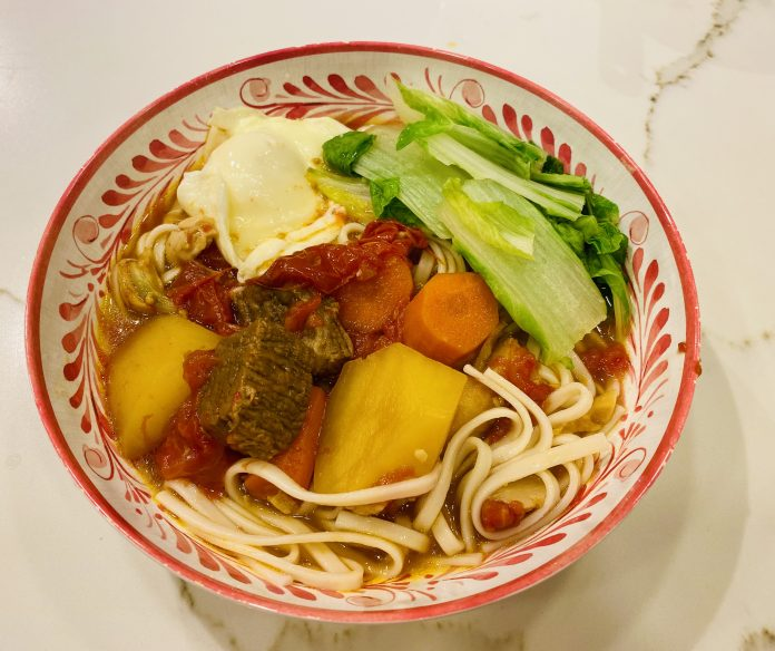 A bowl filled with noodles, pieces of beef, potato, carrot, tomato, and green Chinese veggies.