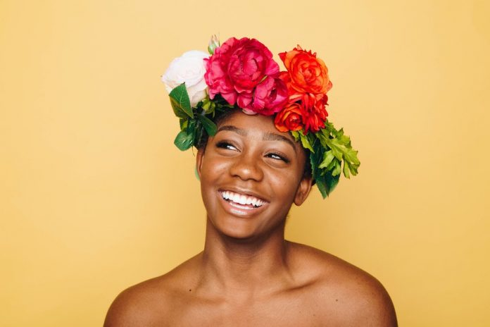 lady with glowing skin and flower crown, soft yellow background