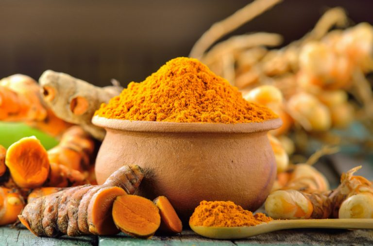 Turmeric root sitting on a table around a bowl and spoon filled with turmeric powder.