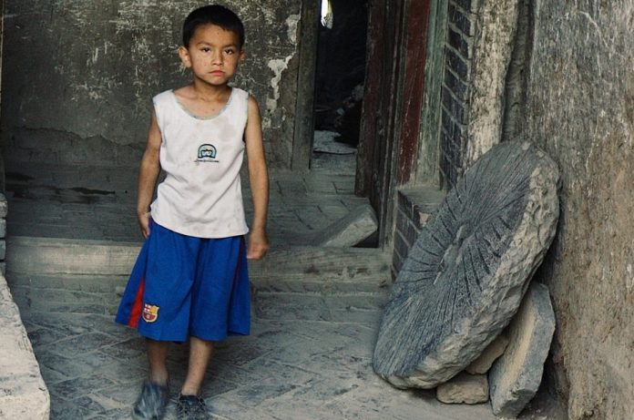 Young Uyghur boy in front of his home in Kashgar, China.