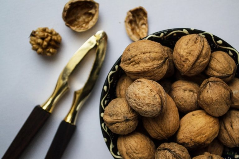 bowl of walnuts with a nut cracker on a table
