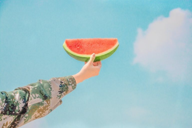 hand holding a slice of watermelon up highs blue sky background with white cloud