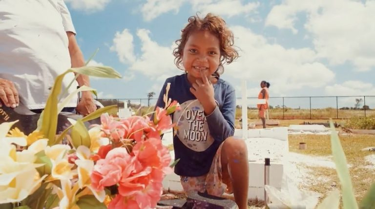 Aboriginal boy with fresh flowers by a grave smiling it is a bright and sunny day