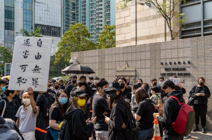 Family and supporters, mostly wearing black clothing, stand outside the West Kowloon Law Courts Building in Hong Kong to wait for the results of the trial of the 47 pro-democracy activists who organized a primary election in July 2020.