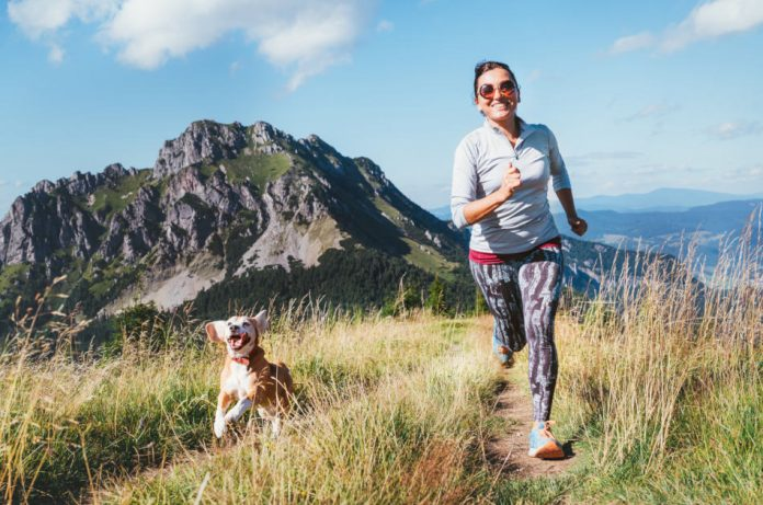 Happy smiling female jogging on a mountain trail with her beagle.