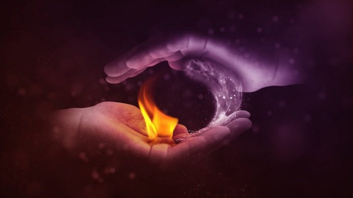 two hands cupped above each other one holds ice one holds fire symbolic of a yin yang symbol