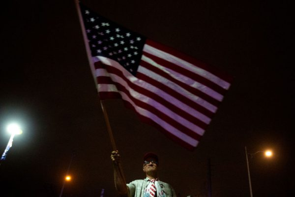 A supporter of President Donald Trump waves a flag as demonstrators gather to protest election results at the Maricopa County Elections Department office on November 6, 2020 in Phoenix, Arizona.