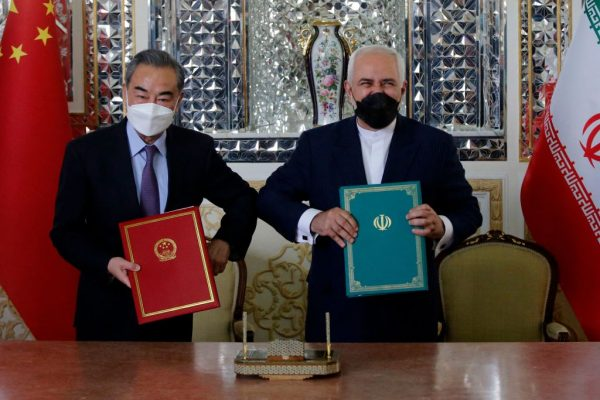 Iranian Foreign Minister Mohammad Javad Zarif (R) and his Chinese counterpart Wang Yi, pose for a picture after signing an agreement in the capital Tehran, on March 27, 2021.