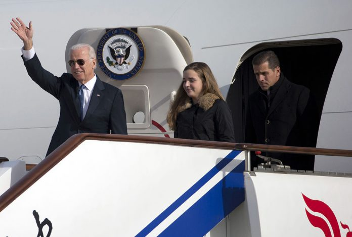 U.S. Vice President Joe Biden waves as he walks out of Air Force Two with his granddaughter Finnegan Biden and son Hunter Biden (R) on December 4, 2013 in Beijing, China.