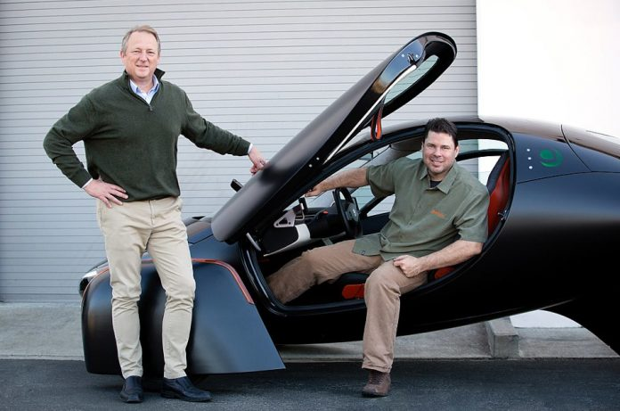 Co-founders of Aptera Motors, Steve Fambro and Chris Anthony, with a black Aptera 3-wheeled Electric Vehicle.
