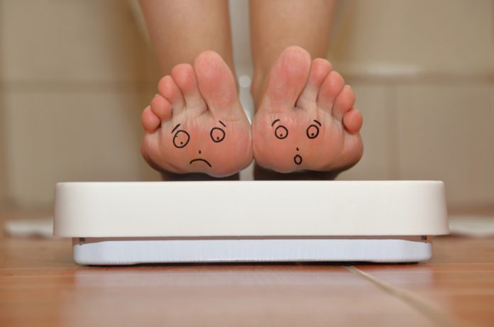 A woman tipped back on her heels to show the soles of her feet while standing on the bathroom scales.