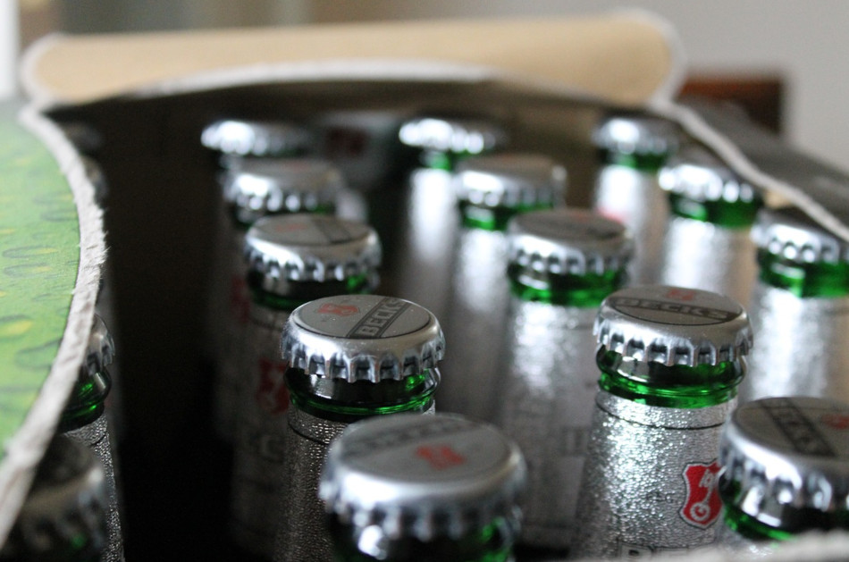 An open case of Beck's beer in green glass bottles with silver bottle caps.