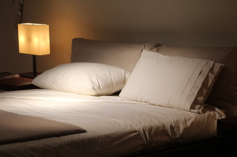 A double bed with sheets turned down and bedside lamp turned on.
