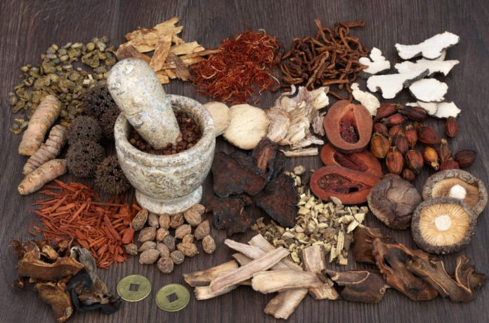 Traditional chinese herbal medicine selection with mortar and pestle on oak background.