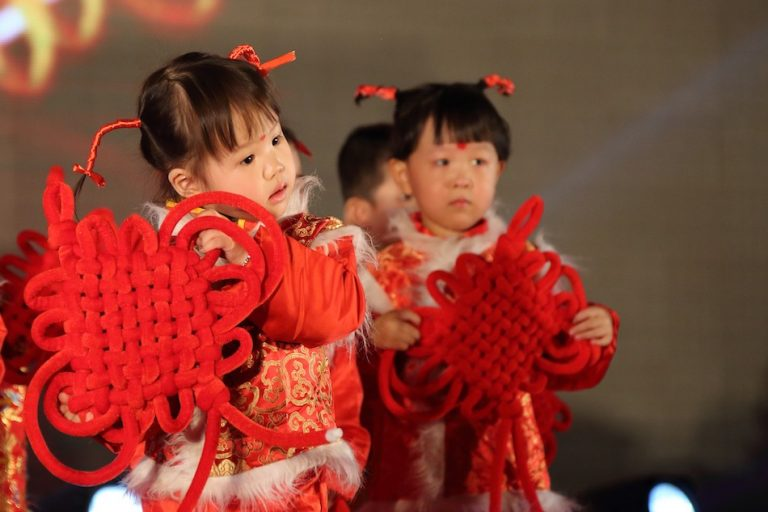 2 chinese girls hold a large chinese knot design they have pigtails with red ribbon wrapped around and wear traditional red chinese costume