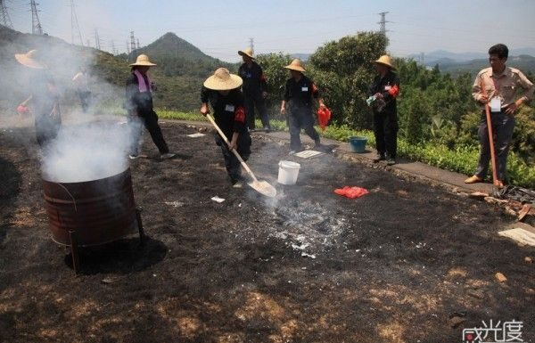 Qingming festival Sanitation workers clean up after a grass fire got out of hand.