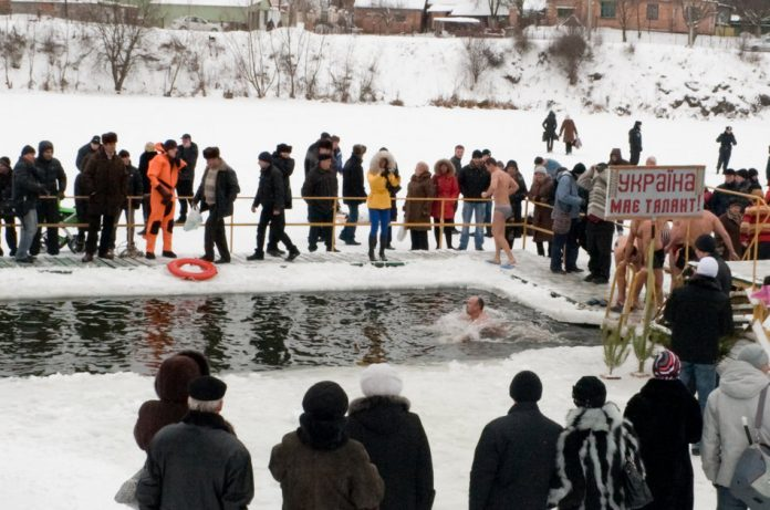 A group of people gathered outside in winter to watch as member of a swim club swim in a lake.
