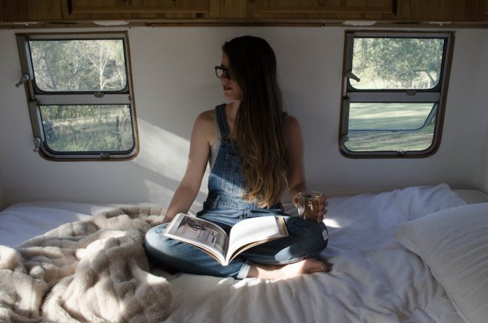 girl holds cup of tea as she sits on her bed in a caravan
