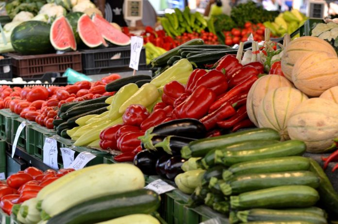 A selection of melons, tomatoes, zuchini, eggplant, and various kinds of peppers at a stall at a farmer's market.