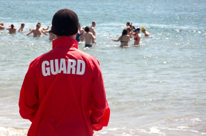 """A man wearing a brown knit cap and a red jacket with the word """"guard"""" on the back looks on as people swim in the ocean."""