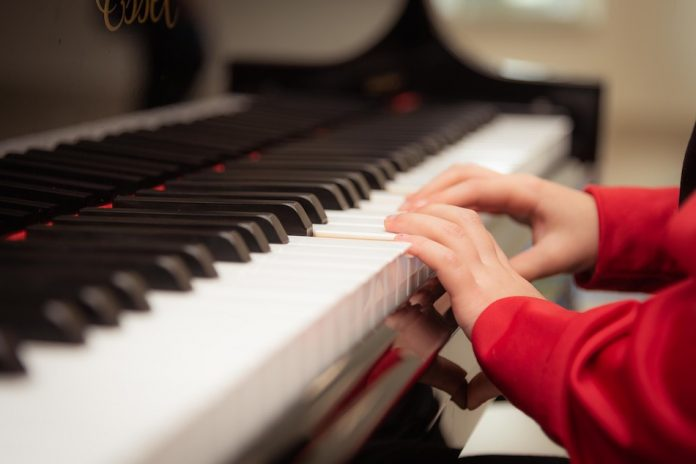 A childs hands playing a piano
