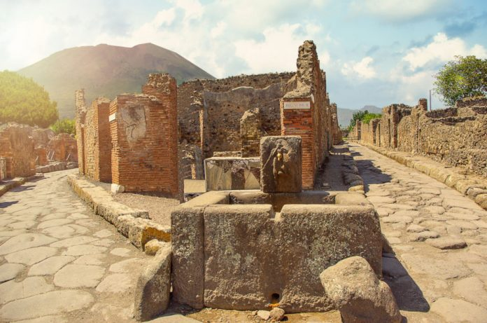 Ancient water well in Pompeii with Mount Vesuvius in the background.