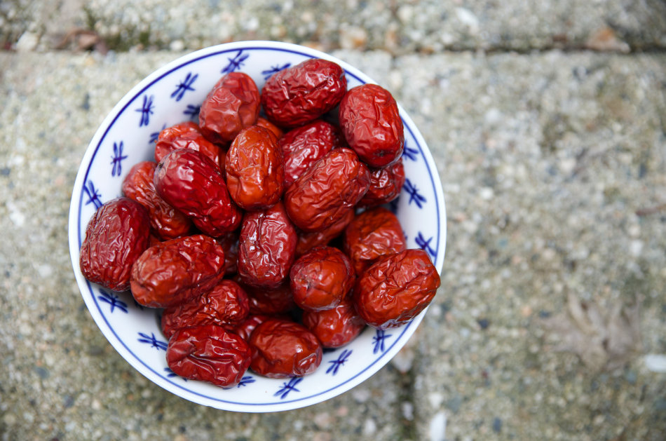 A white porcelain bowl decorated with blue dragon flies is filled with red Chinese dates.