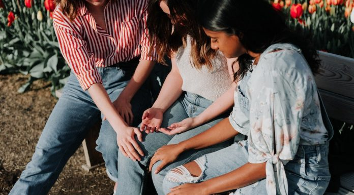 3 female friends sit on a bench the two girls on the outside rest hands on girl in the middle to support her through feelings of anxiety
